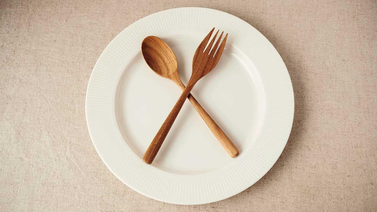 Gekreuzte Holzgabel und Holzlöffel symbolisieren Fasten und Verzicht