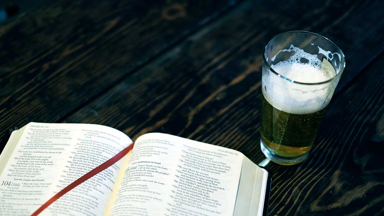offene Bibel und Glas mit Bier auf einem Holztisch