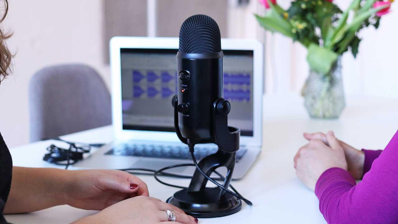Zwei Frauen mit einem Mikrofon dazwischen nehmen einen Podcast auf