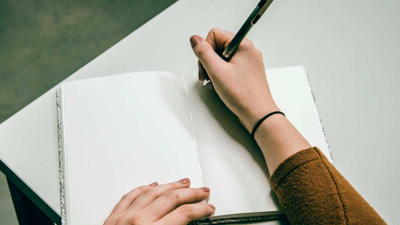 Hand mit Kugelschreiber beginnt in ein Notizbuch zu schreiben