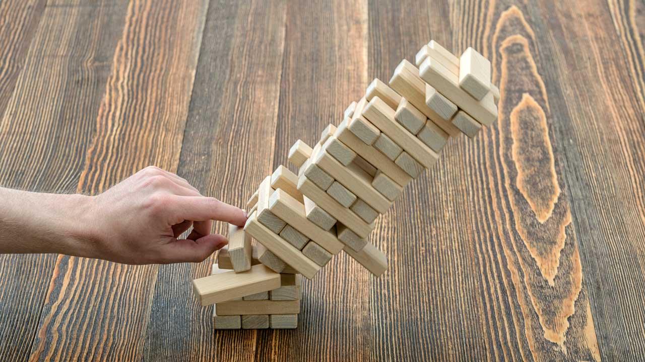 Hand stösst Turm aus Holzklötzchen um