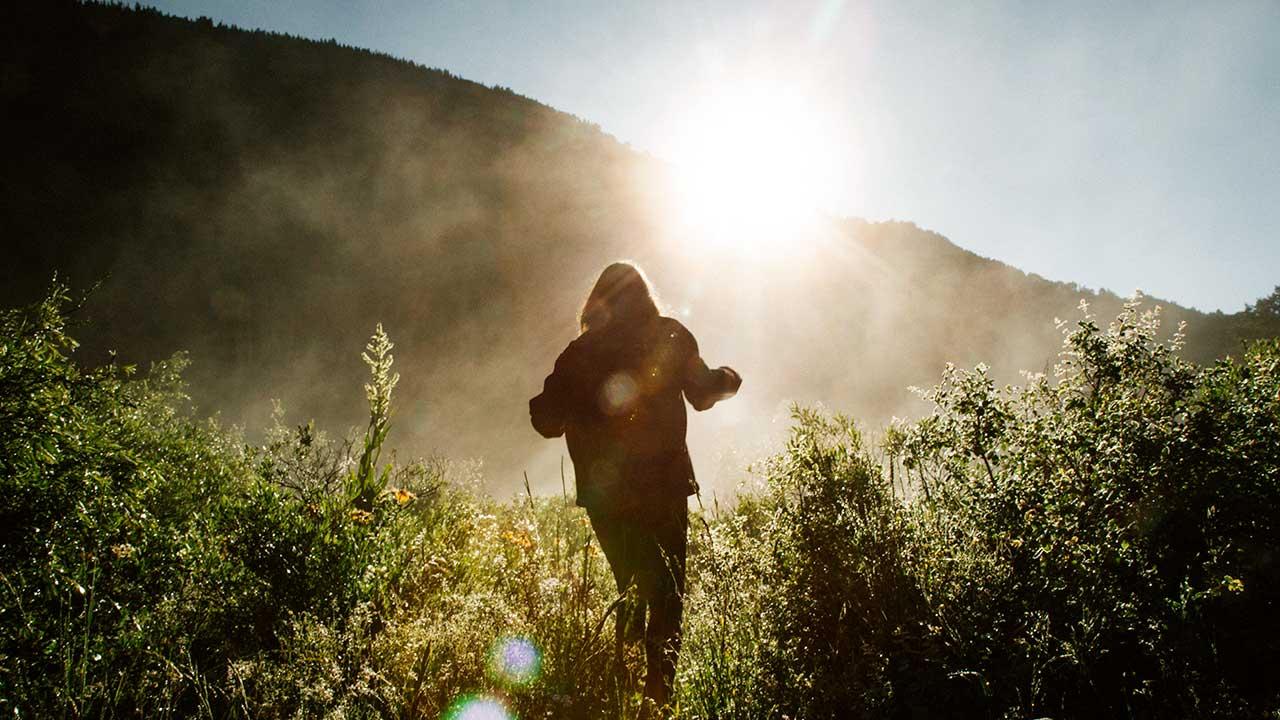 Frau läuft durch die Wiese, über dem Bergrand taucht die grelle Sonne auf