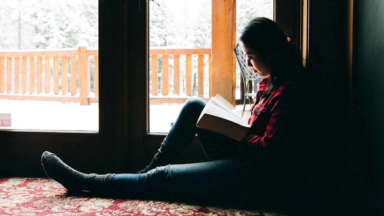 Junge Frau liest sitzend und in Ruhe Bibel