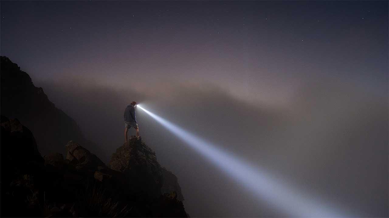 Mann steht auf einem Berg und leuchtet mit seiner Helmlampe abwärts
