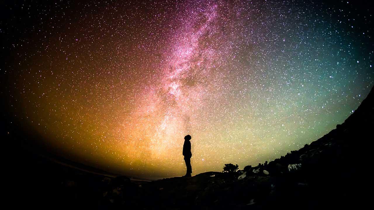 Ein Mensch blickt hoch zu einem mehrfarbiger Sternenhimmel