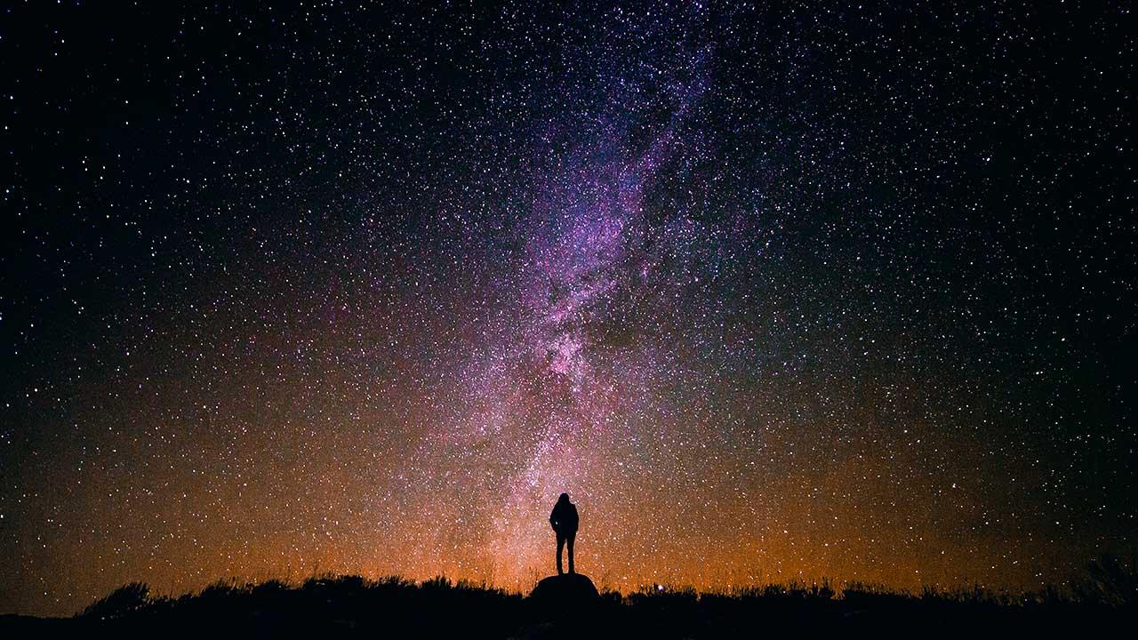 Mensch als kleine Silhouette blickt in einen grossen Sternenhimmel