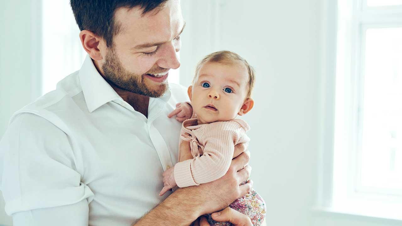 Vater freut sich an seiner Baby-Tochter, welche er in seinen Händen hält