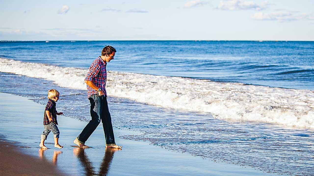 Vater und Sohn laufen am Strand zu den Wellen hin