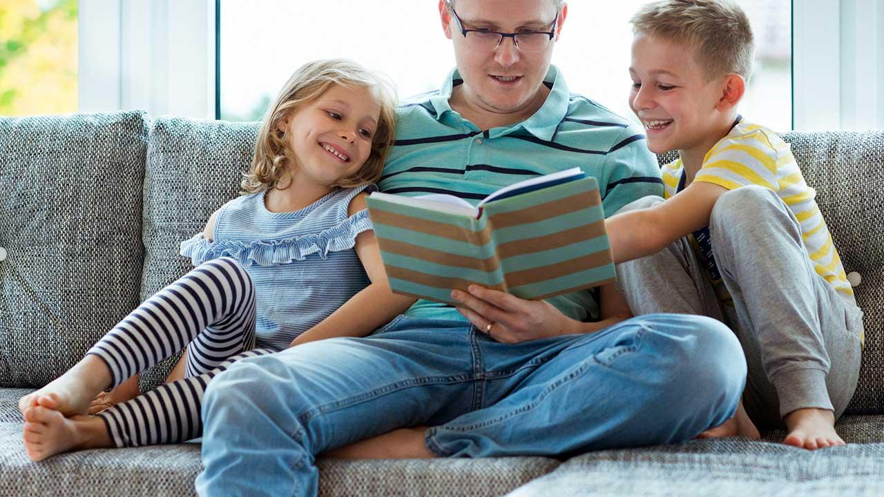 Vater sitzt mit Tochter und Sohn auf dem Sofa und liest aus einem Buch vor