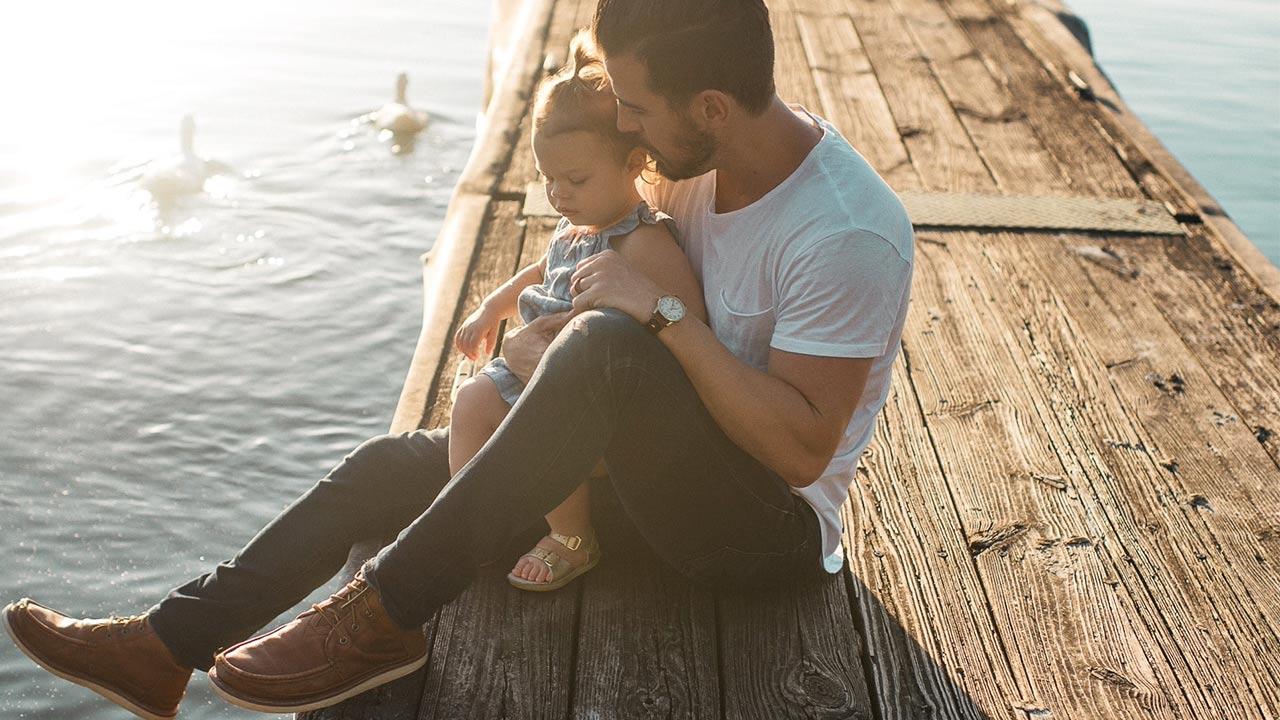 Vater und Tochter sitzen auf einem Steg | (c) unsplash