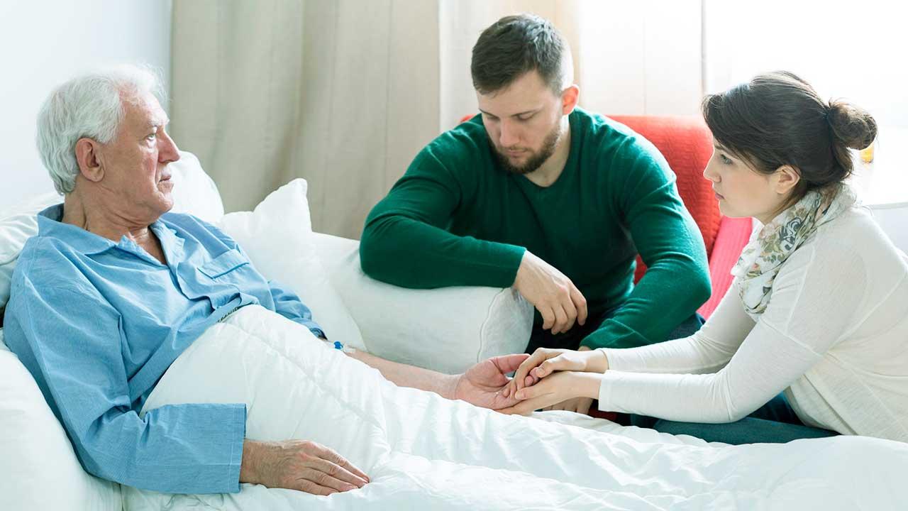 Erwachsene Kinder sitzen am Krankenbett ihres Vaters, die Stimmung ist ernst