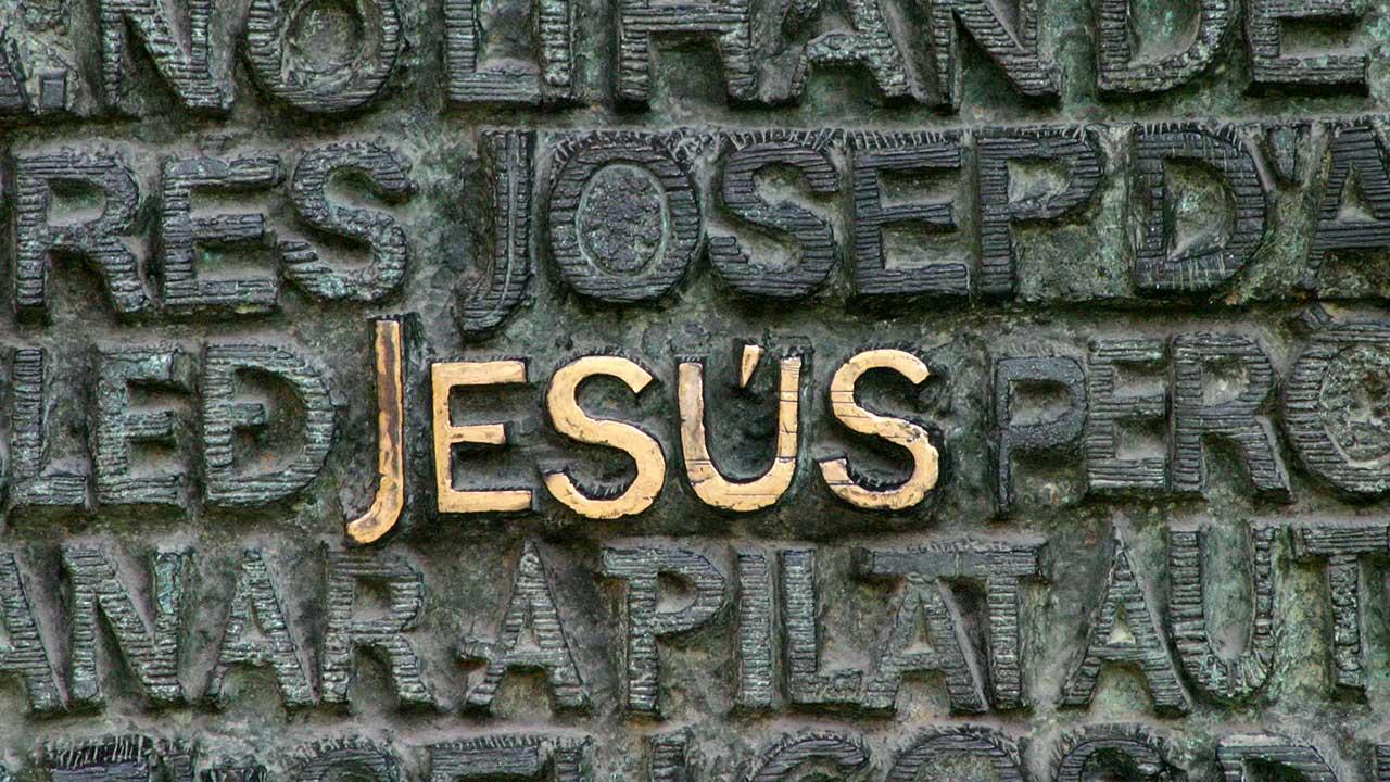 Steinwand mit Wörtern, wo das Wort Jesus golden hervorsticht