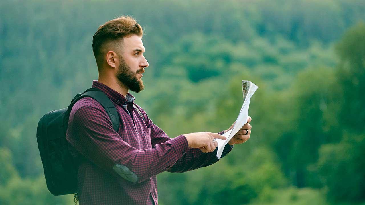 Jüngerer Mann blickt auf Karte, um den weiteren Weg zu entscheiden