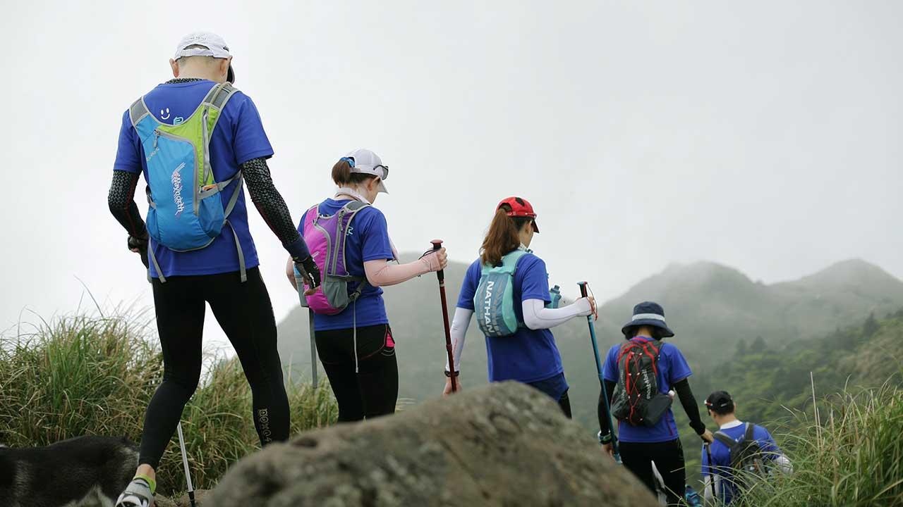 Wandergruppe unterwegs in Sportkleidung und Stöcken