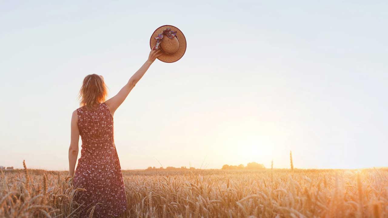 In einem Getreidefeld winkt eine Frau mit ihrem Hut zum Abschied