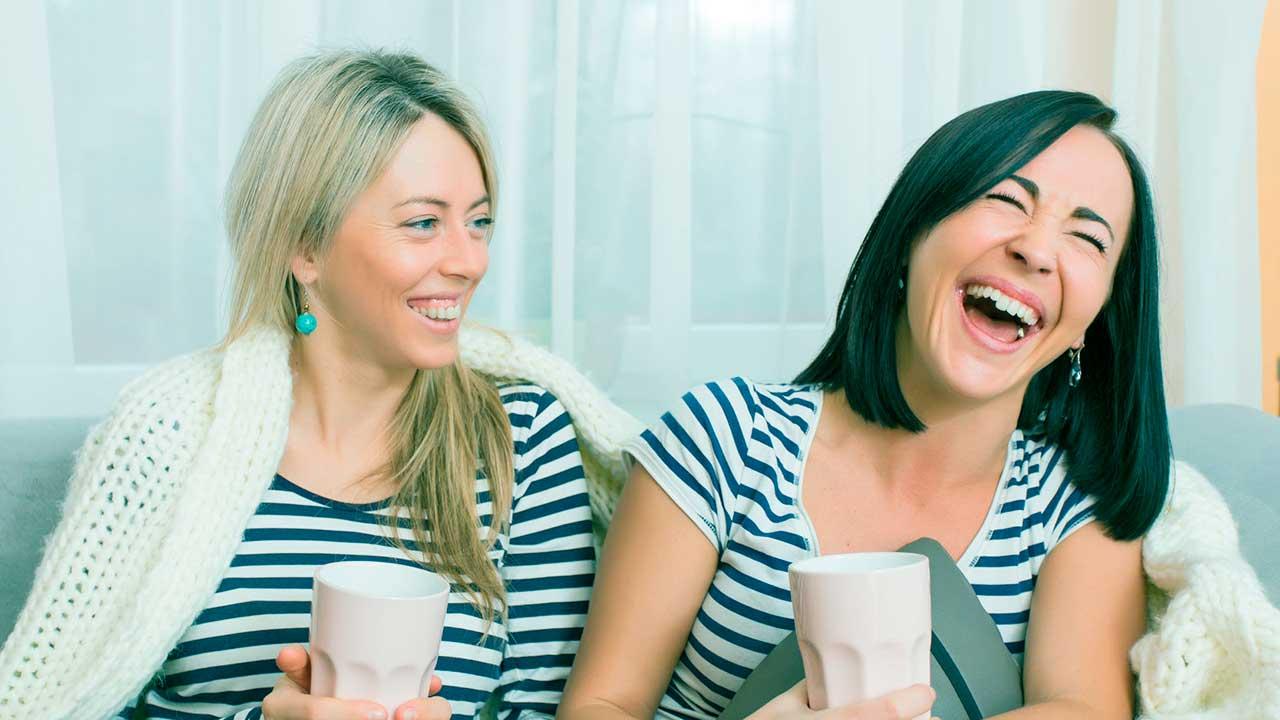 Zwei junge Frauen sitzen auf dem Sofa und haben eine gute Laune