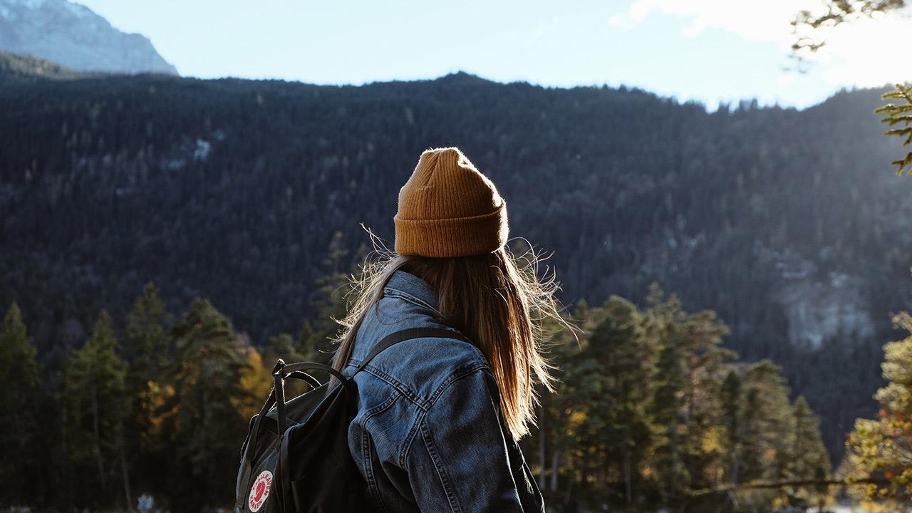 Eine Frau betrachtet die bergige Landschaft.