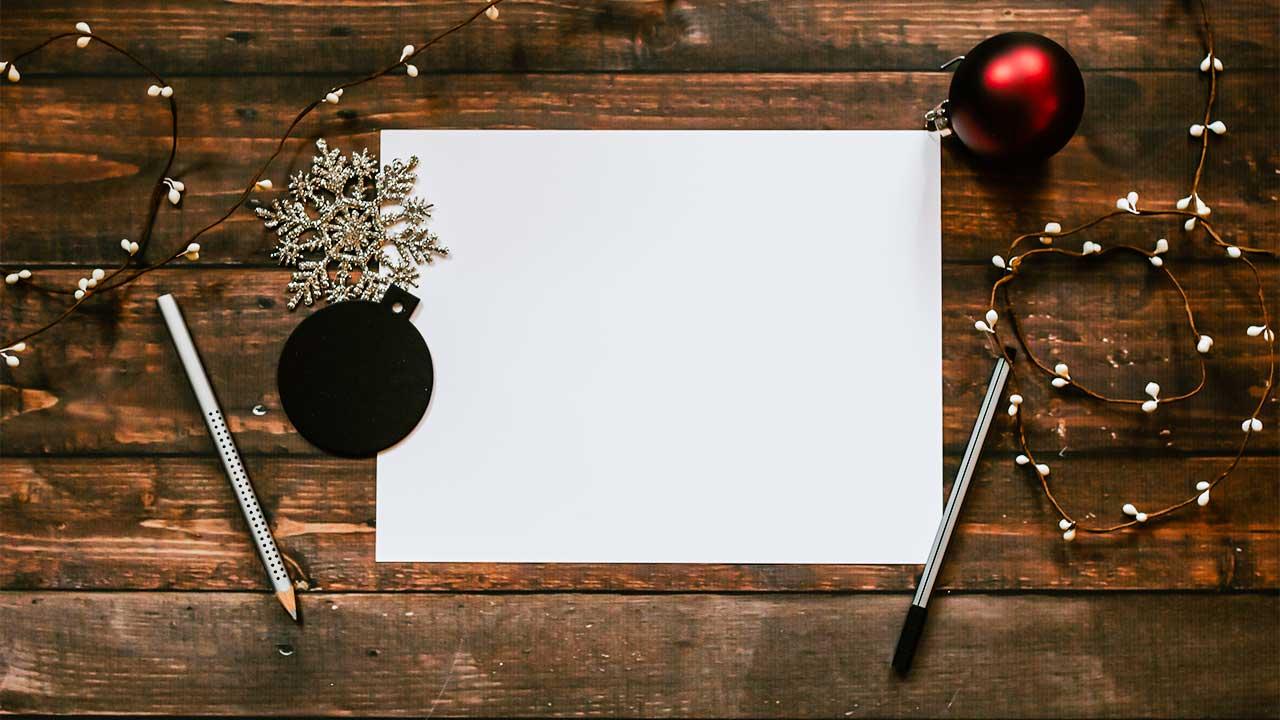 Blatt und kleine Adventsutensilien auf einem Holztisch