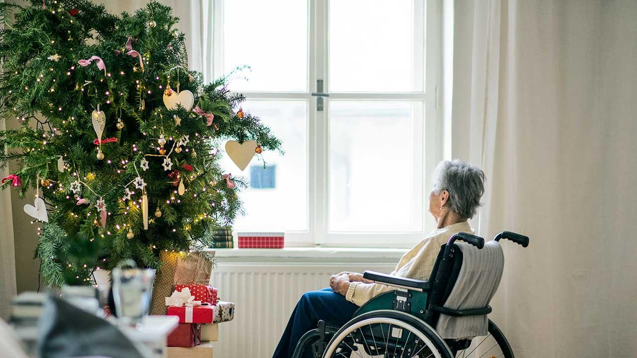 Seniorin im Rollstuhl sitzt allein vor einem Christbaum