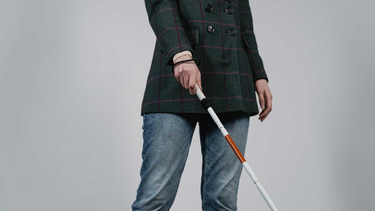 Ein Mann hält einen Blindenstock in der Hand