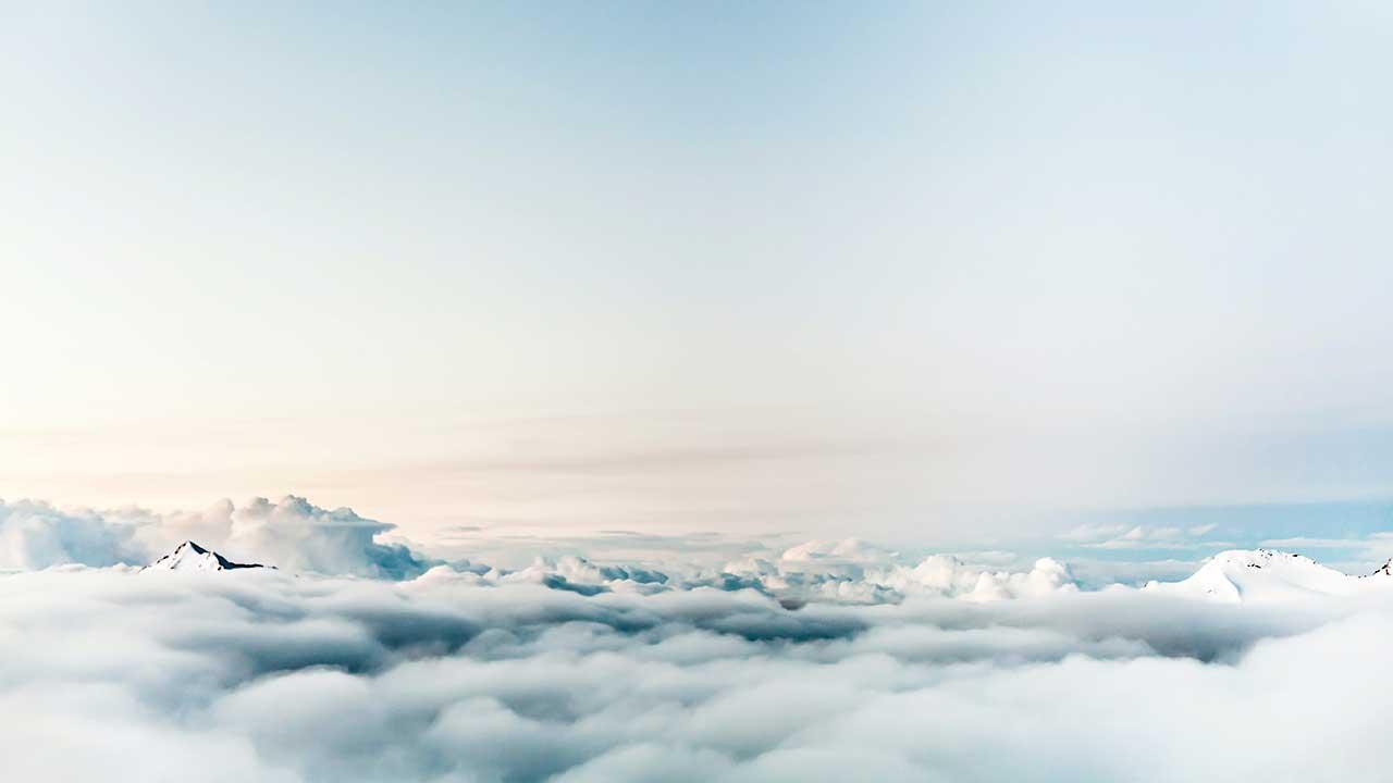 Blick über Wolken und verschneite Berggipfel