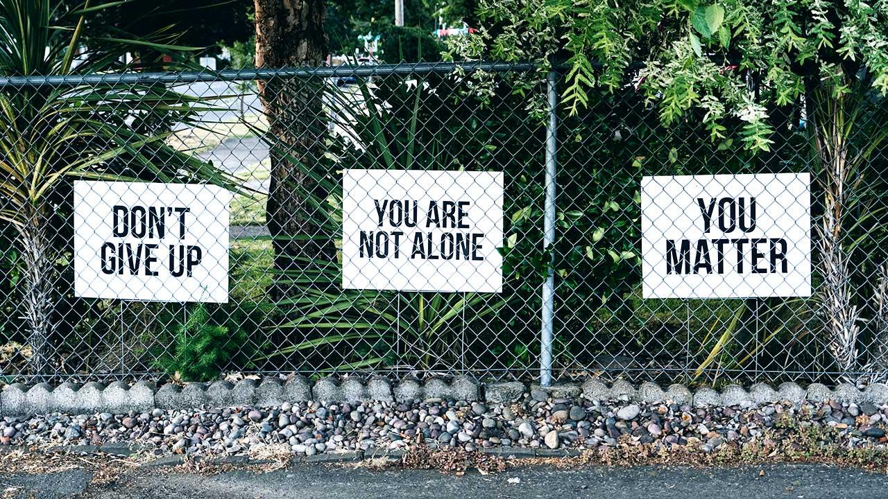 Schilder auf einen Zaun in Englisch, welche ermutigen