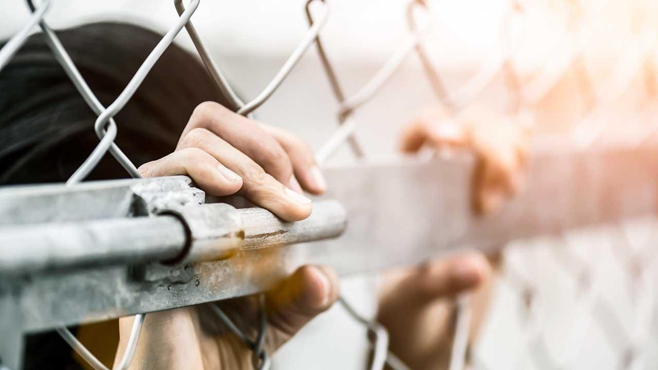 Frauenhände umfassen Gitterzaun