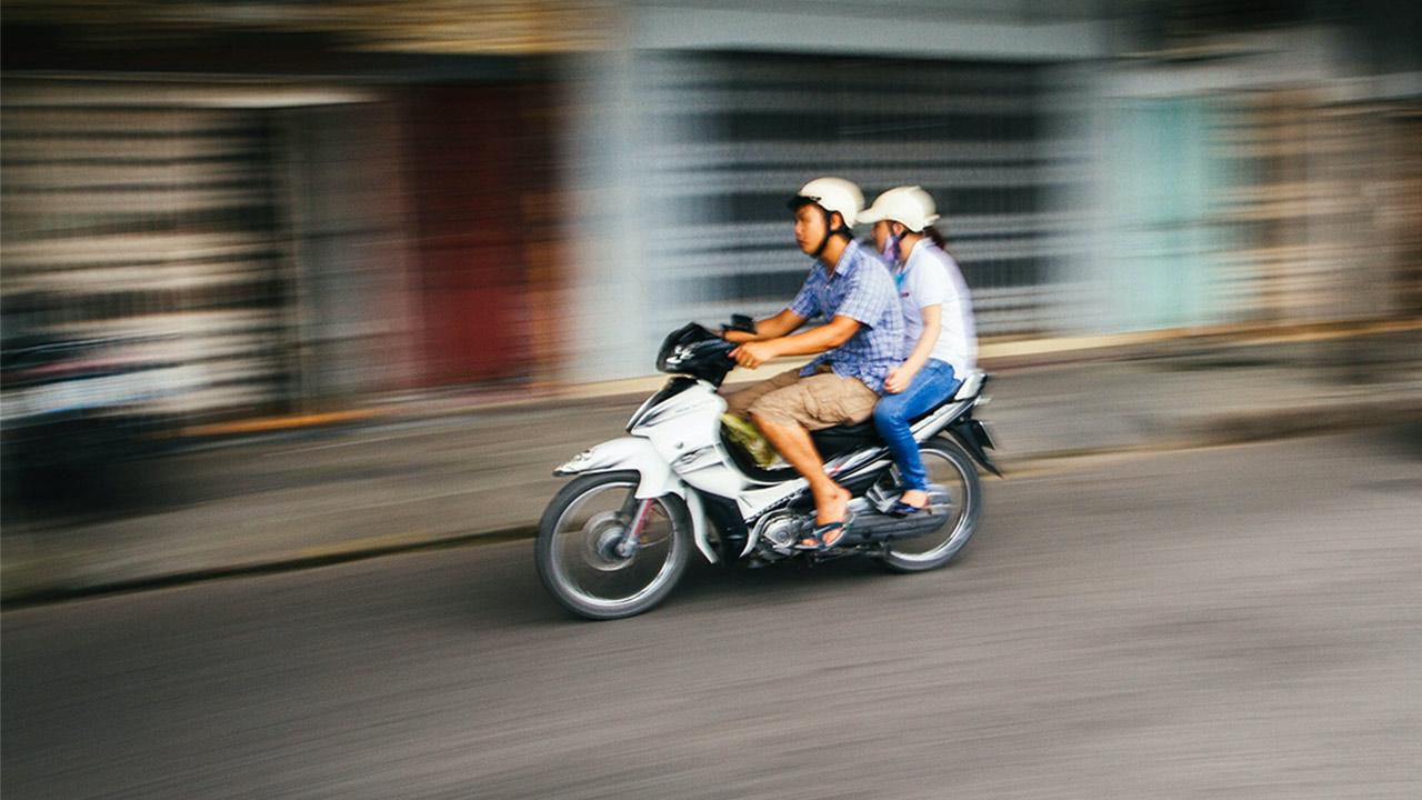 Zwei Personen fahren zusammen Motorrad