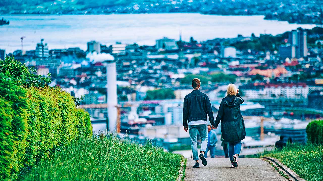 Paar spaziert in Höngg, mit Blick auf das Zentrum von Zürich und den See