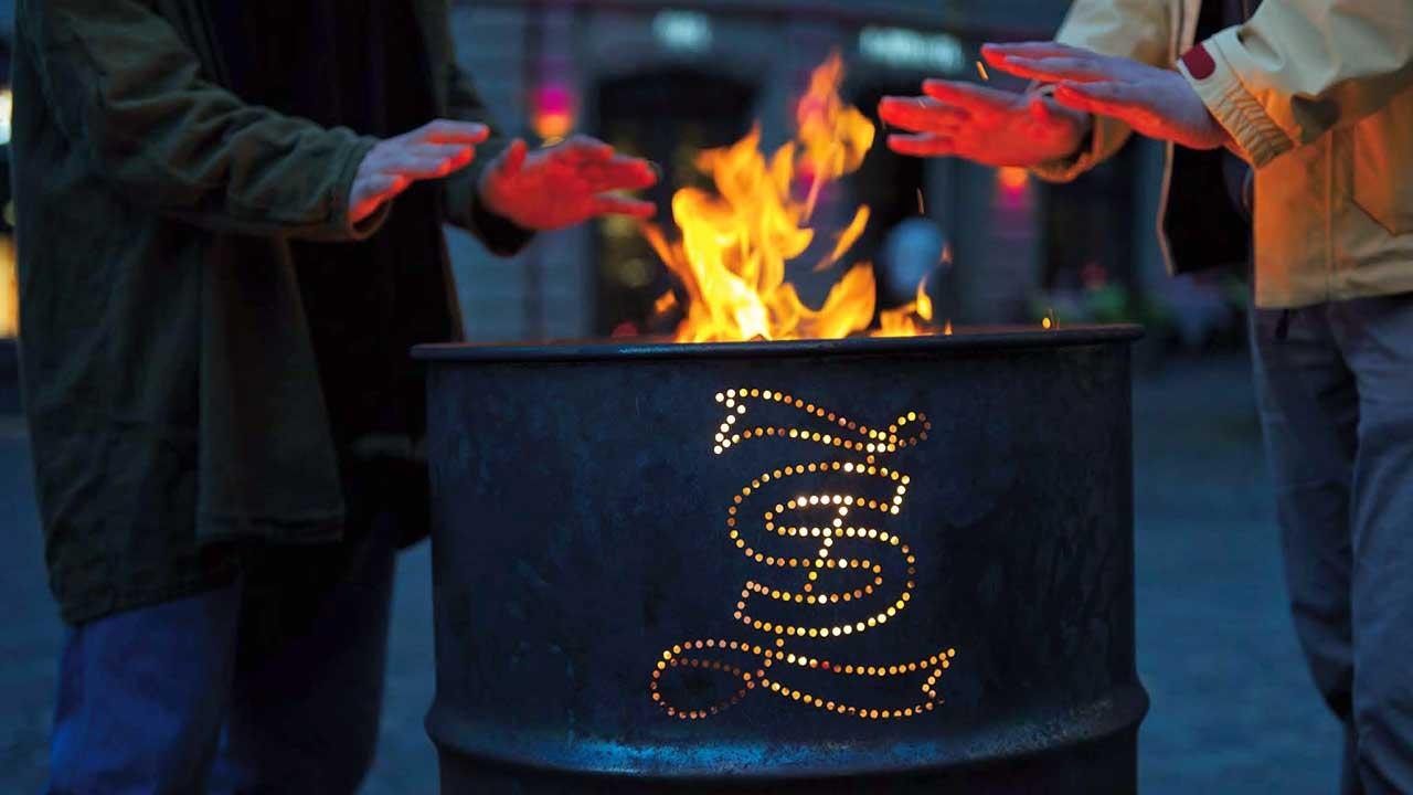 Tonne mit Feuer, an welchem sich Hände wärmen