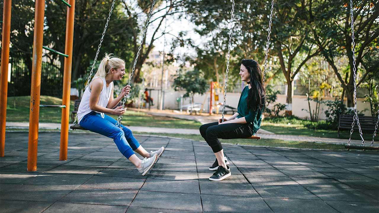Zwei junge Frauen sitzen auf Schaukeln und sind fröhlich