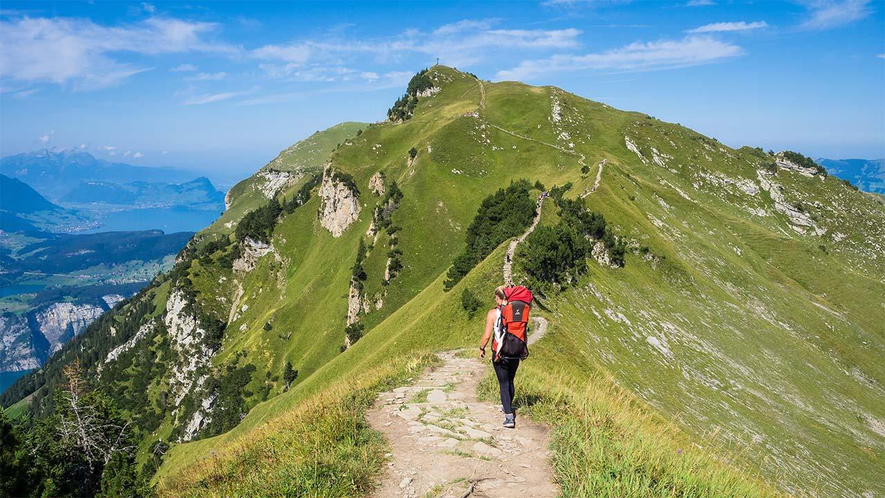 Eine Frau wandert in Richtung Berggipfel.