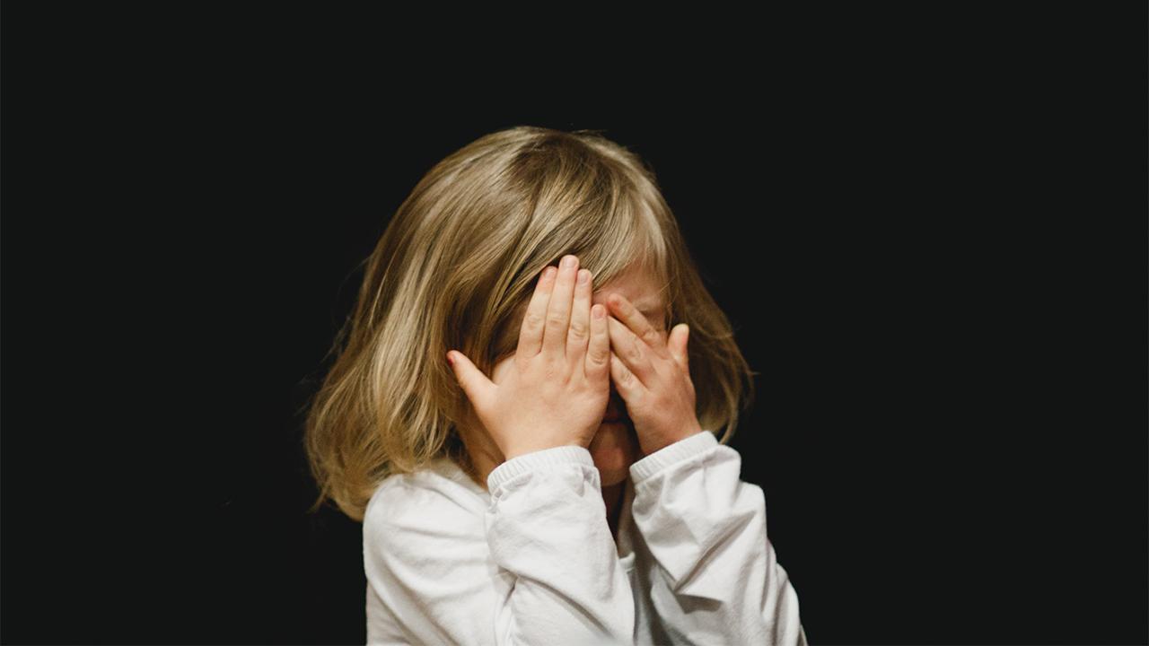 Ein Mädchen hält sich schützend die Hände vor das Gesicht