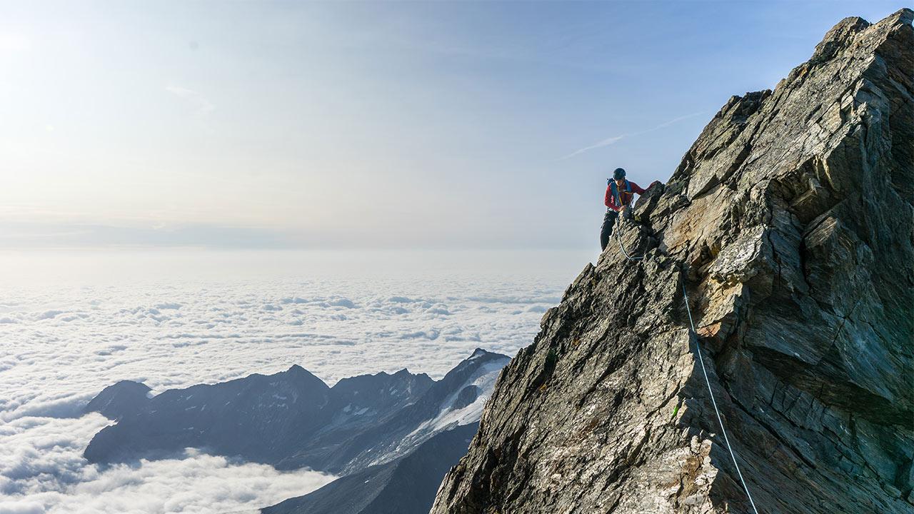Ein Wanderer hölt sich an einem Felsen fest.