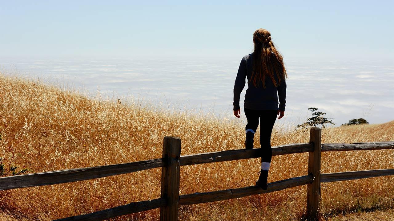 Eine Frau steigt über einen Zaun.