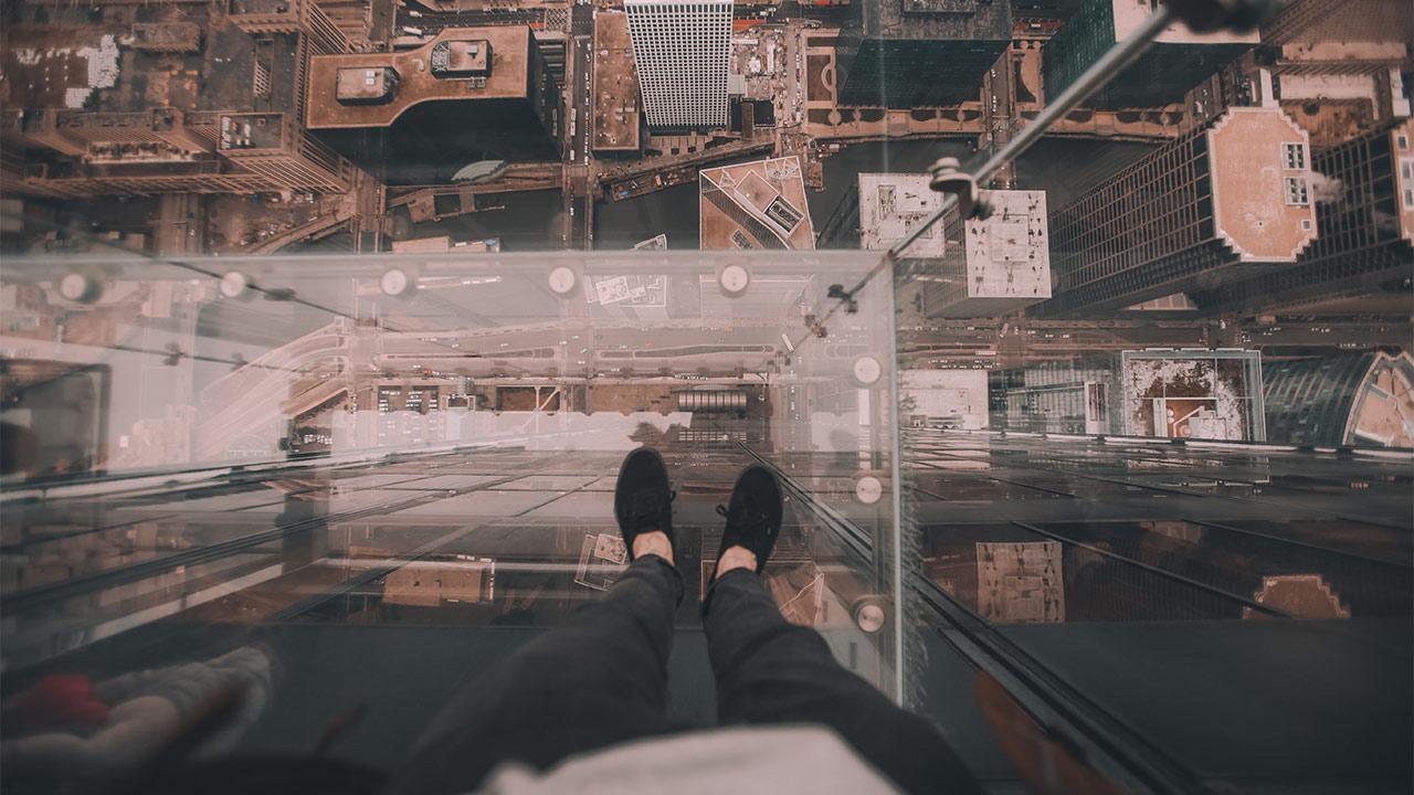 Eine Person steht auf einem Glasboden und schaut in den Abgrund.