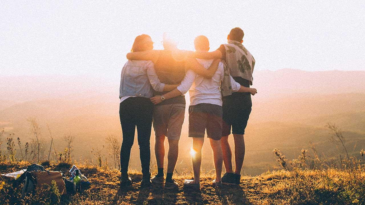 Rückansicht auf vier junge Erwachsene, welche von der Sonne beschienen werden