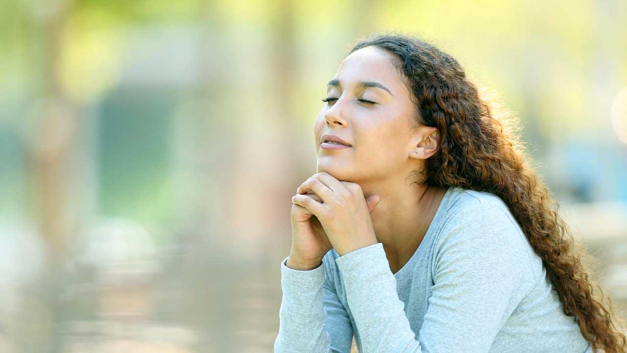 Junge Frau hält Augen geschlossen und ist ausgeglichen