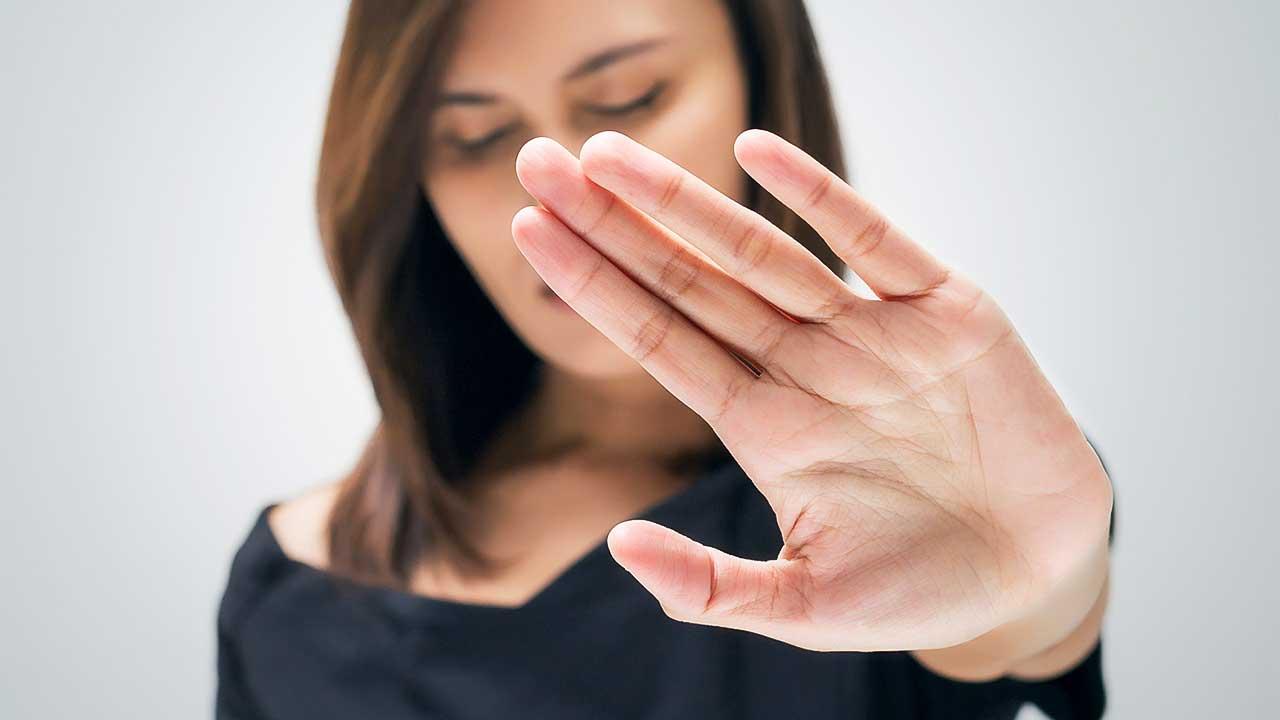Junge Frau streckt Hand aus und sagt damit Nein.