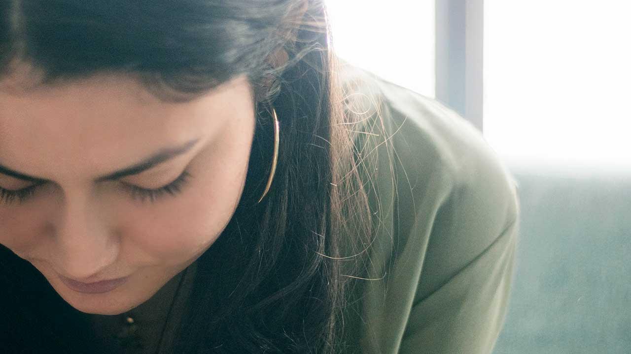 Junge Frau sitzt mit gesenktem Kopf da und betet oder meditiert