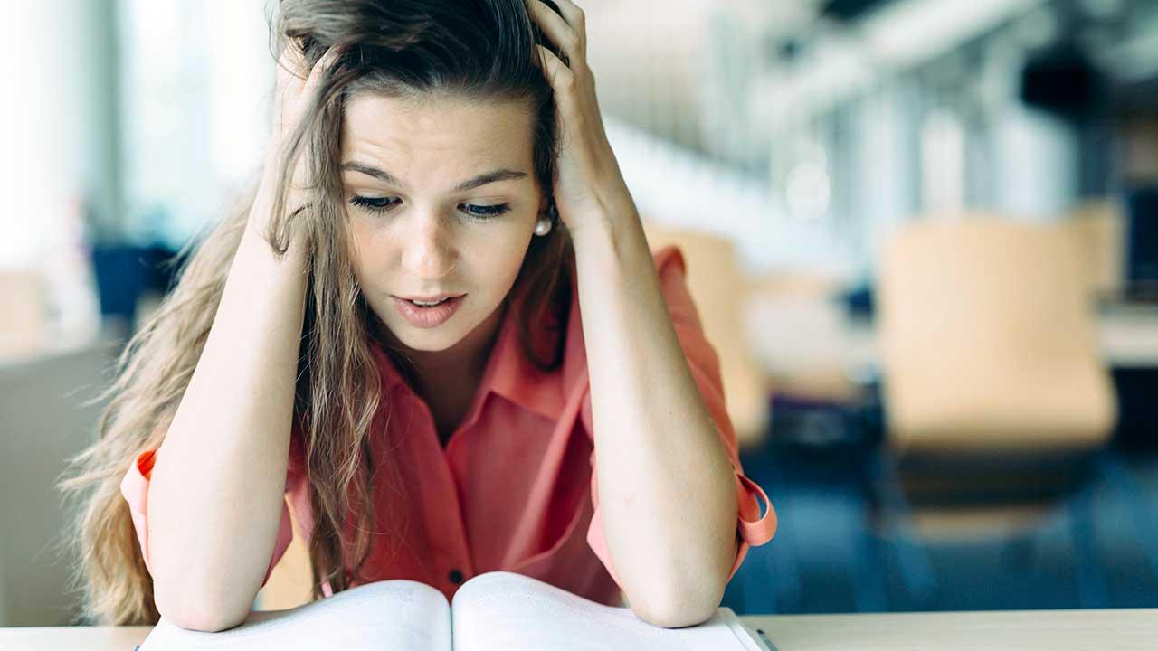 Studentin brütet über Buch und ist herausgefordert