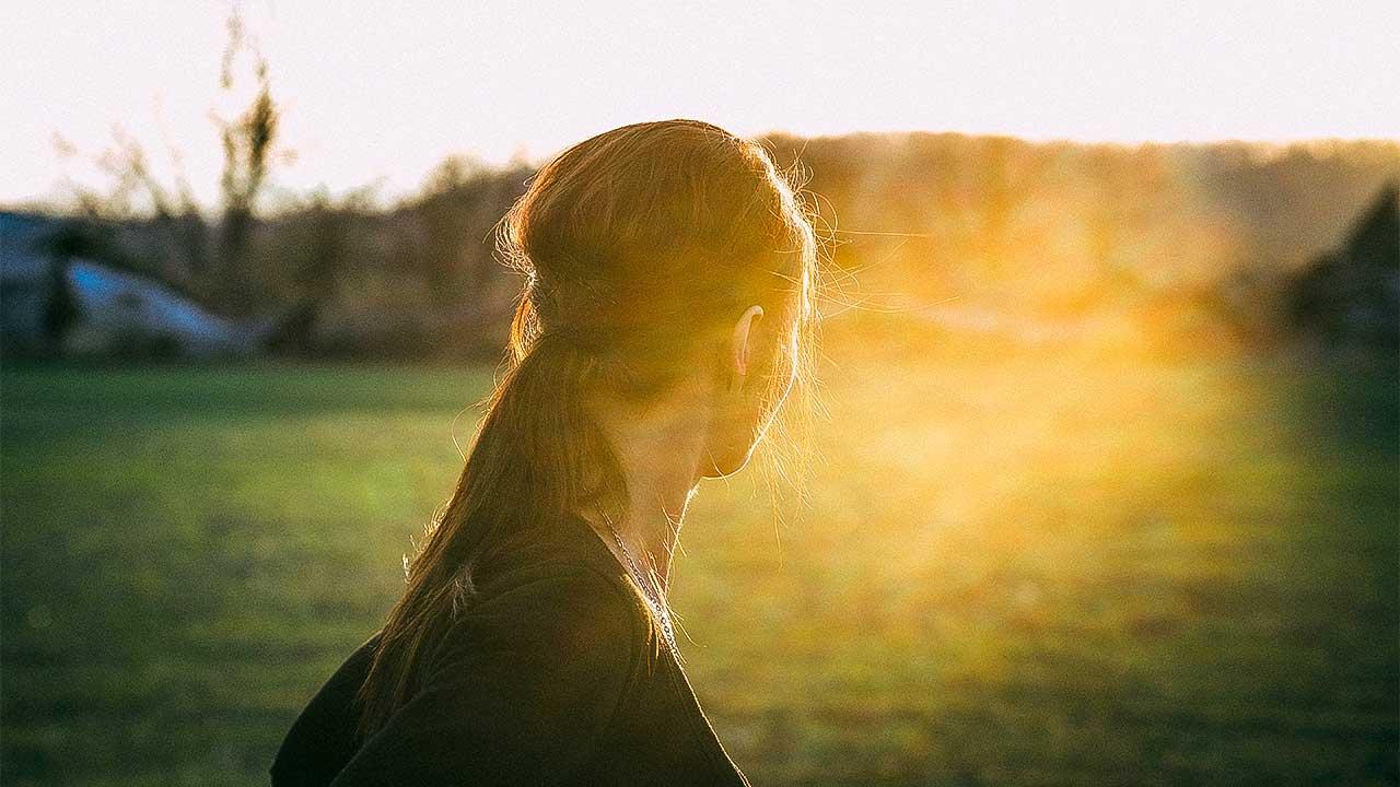 junge Frau blickt auf einer Wiese ins Sonnelicht