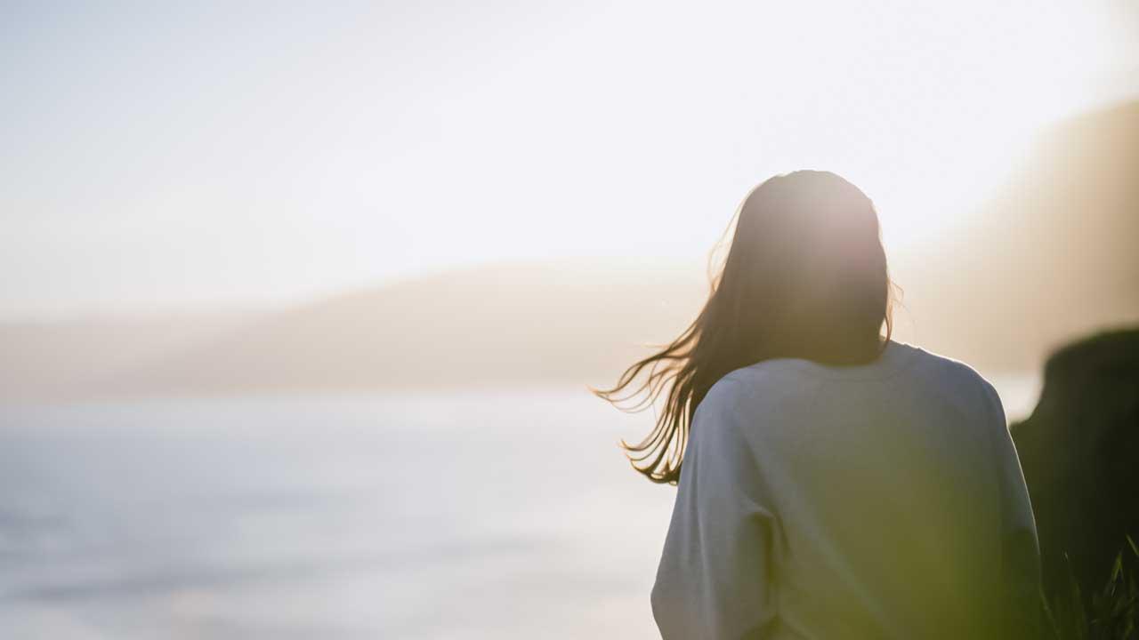 junge Frau sitzt an der Küste und wird von Sonnenlicht beschienen