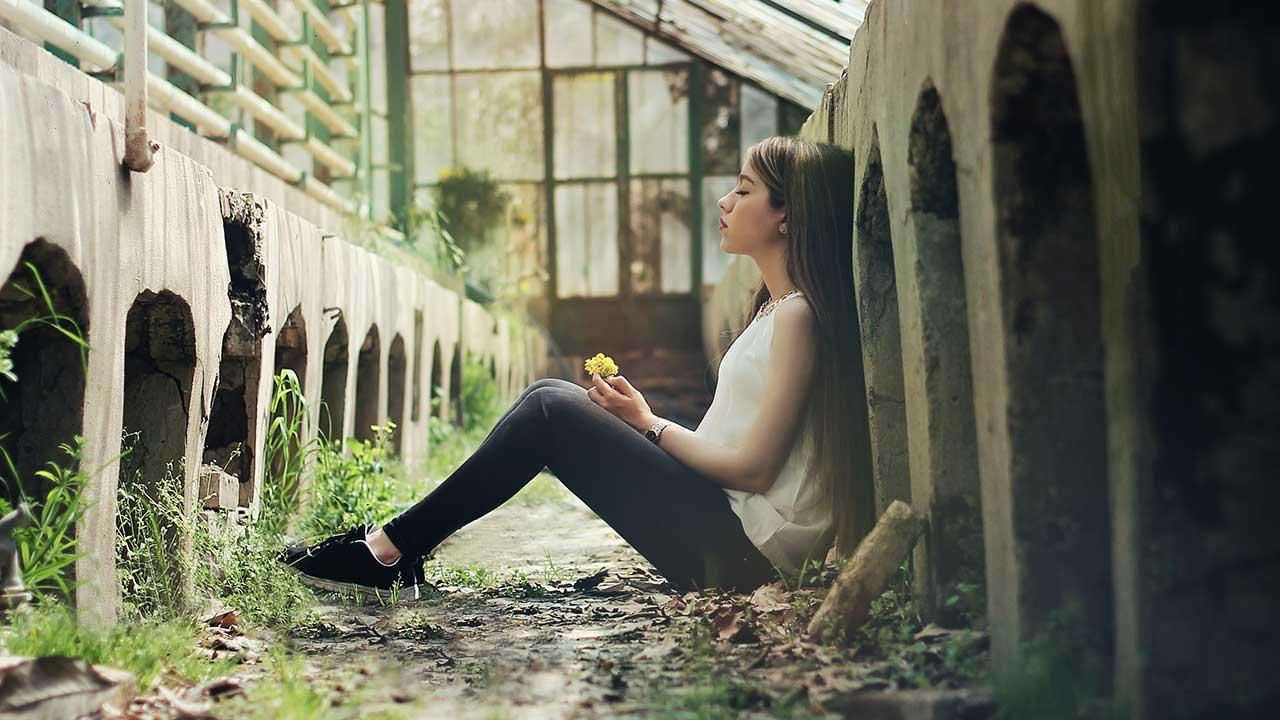 junge Frau sitzt nachdenklich auf dem Boden in einem Gebäude