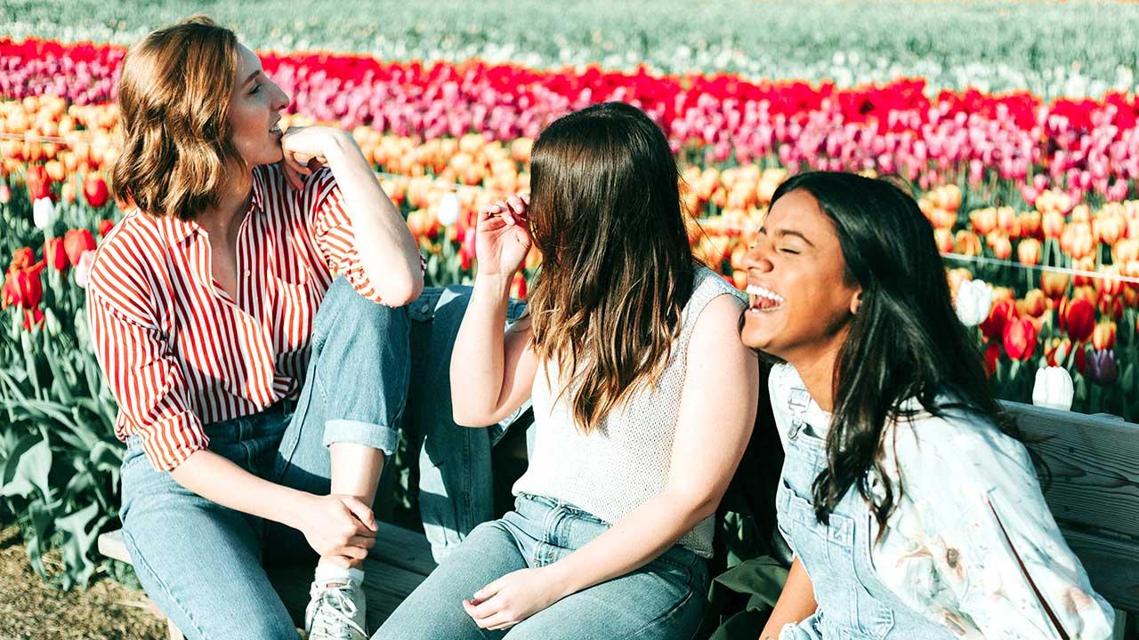 Drei junge Frauen sitzen und haben eine gute Zeit zusammen