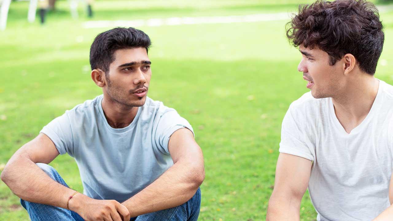 Zwei junge Männer sitzen auf einer Wiese und sind im Gespräch