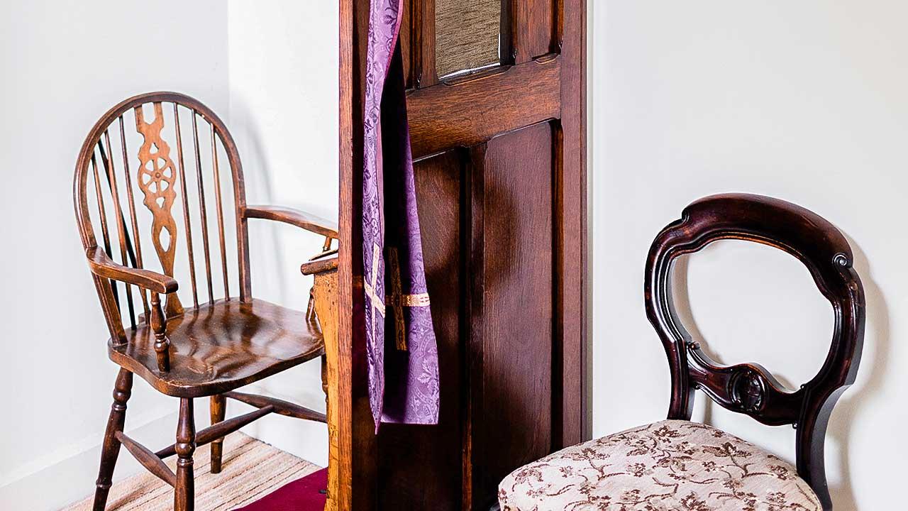 Zwei Stühle und eine Trennwand für eine Beichte