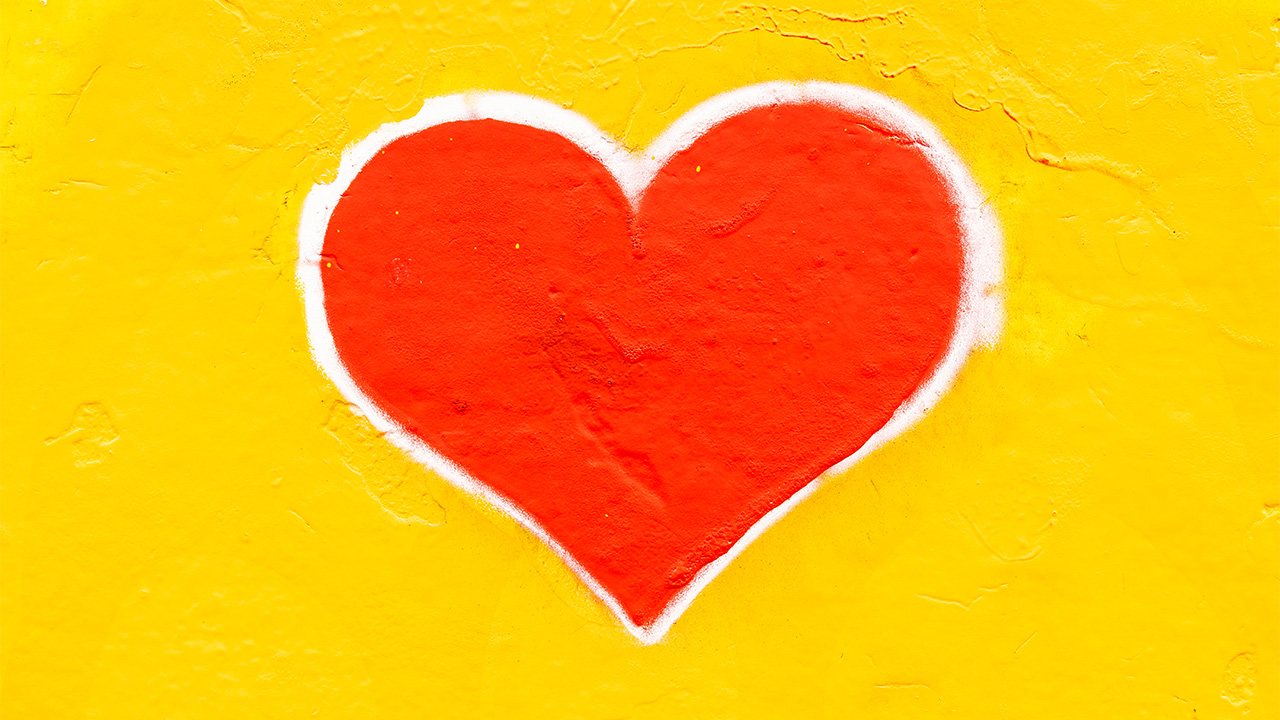 rotes Herz auf gelber Wand