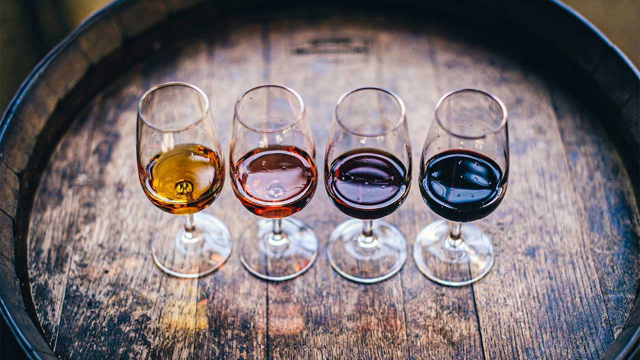 vier Gläser mit verschieden hellen Weinen