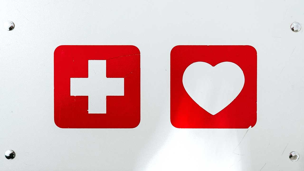 Weisses Kreuz und Herz auf je eigenem rotem Quadrat